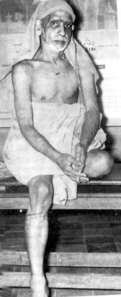 Periyava sitting with one leg down